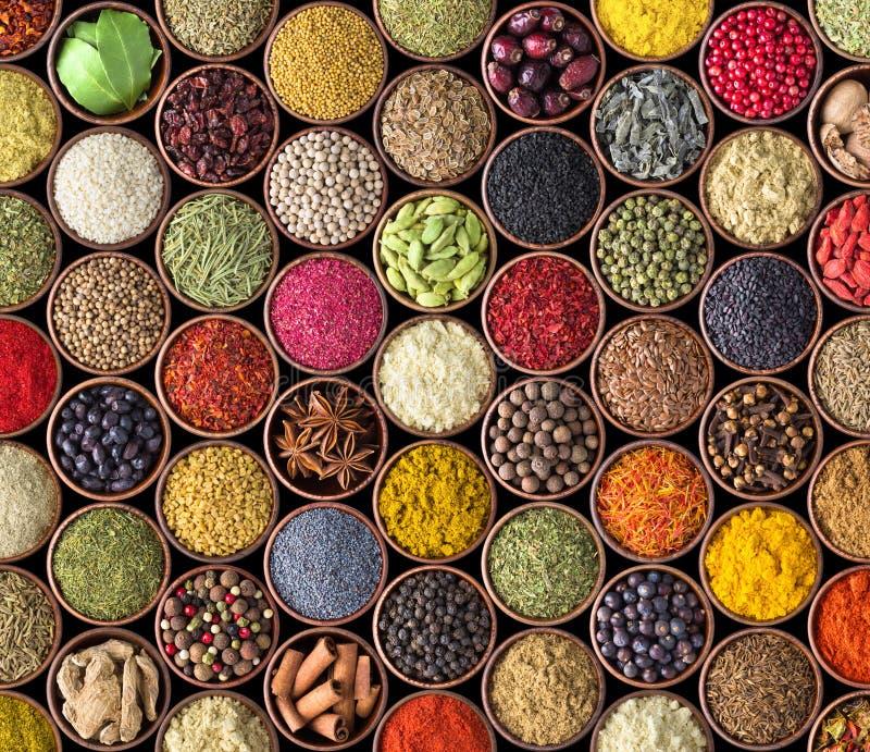 Różnorodni condiments w filiżankach, karmowy tło Pikantności tekstura odizolowywająca na czerni zdjęcie stock