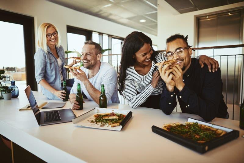 Różnorodni coworkers śmia się piwo i ma pizzę po pracy i obraz royalty free