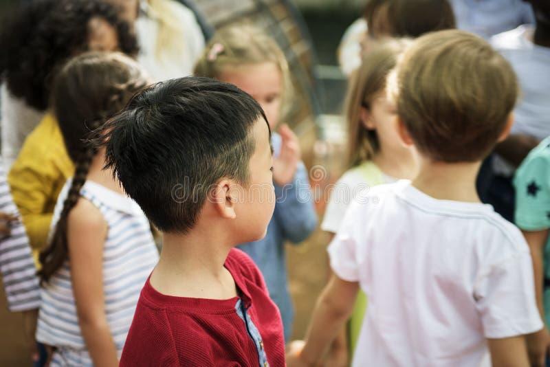 Różnorodni dziecinów dzieciaki przy boiskiem wpólnie obraz royalty free