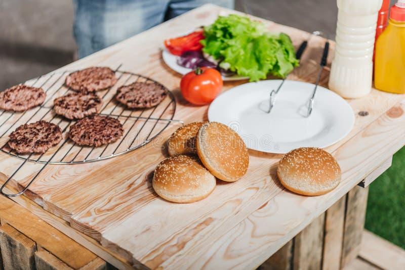 Różnorodni hamburgerów składniki na drewnianym stole zdjęcie stock