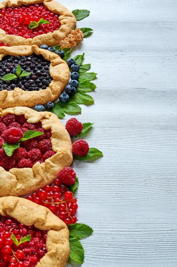 Różnorodni jagod tarts na szarość betonują tło Jarski zdrowy galette dekorował z świeżymi czarnymi jagodami, malinki fotografia royalty free