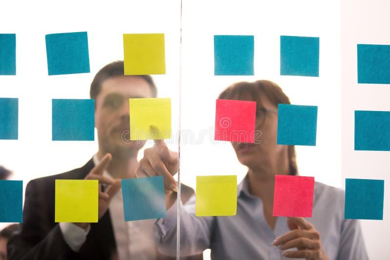Różnorodni koledzy dyskutują pomysły dzielących na kleistych notatkach obraz stock