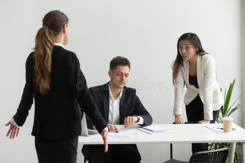 Różnorodni koledzy dyskutuje o niepunktualności lub brakującym deadlin zdjęcie royalty free