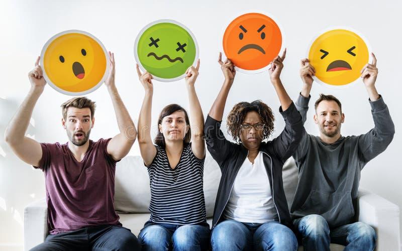 Różnorodni ludzie trzyma emoticon wyrażeniowy zdjęcie royalty free
