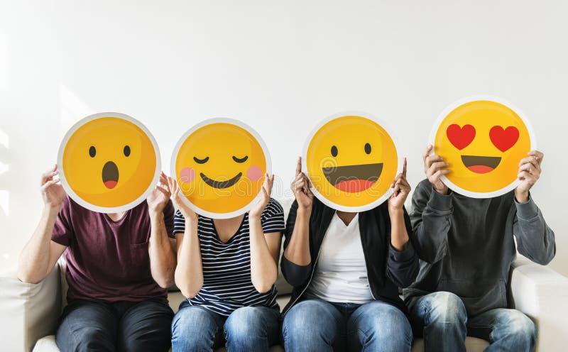 Różnorodni młodzi ludzie trzyma emoticon obraz royalty free