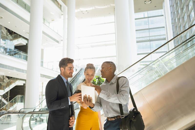 Różnorodni mÅ'odzi przedsiÄ™biorcy z tabletem rozmawiajÄ…cy w nowoczesnym atrium zdjęcie royalty free