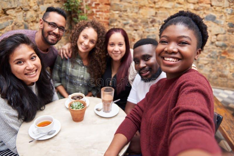 Różnorodni młodzi przyjaciele bierze selfies wpólnie w cukiernianym podwórzu obrazy stock