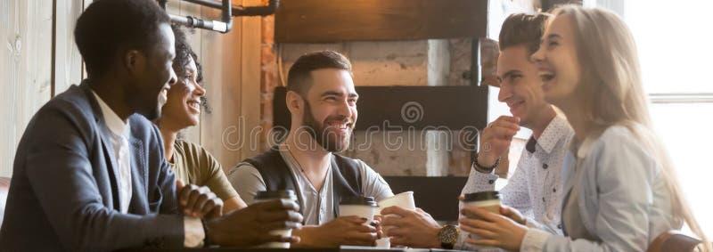 Różnorodni millennial rozochoceni przyjaciele wydaje czas wolnego wpólnie przy kawiarnią obraz royalty free