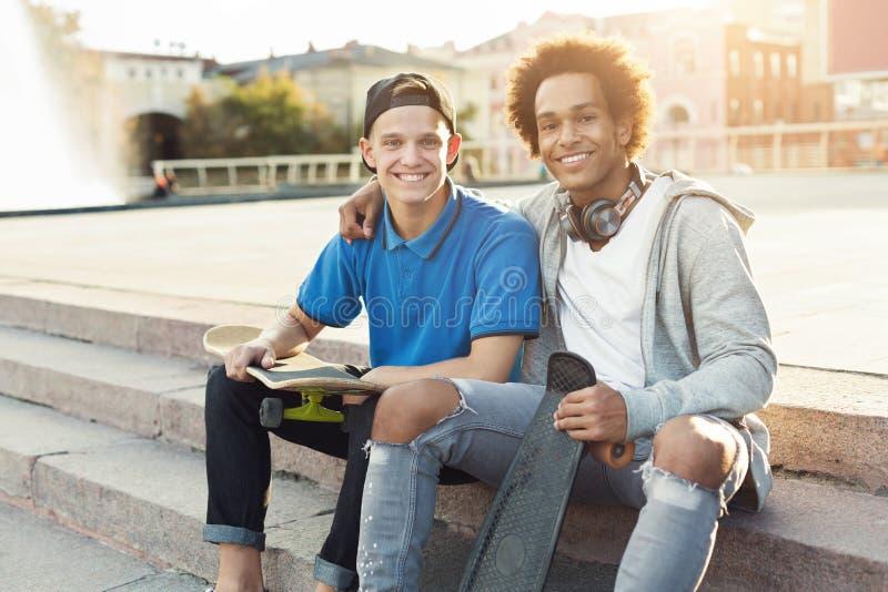Różnorodni nastoletni przyjaciele siedzi outdoors z łyżwami fotografia stock