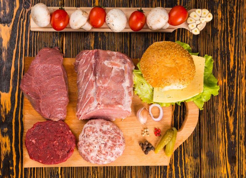 Różnorodni surowi mięsa na tnącej desce dla kanapki obraz stock