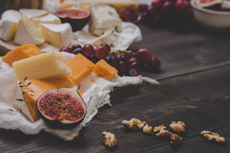 Różnorodni typ ser z owoc i dokrętkami na drewnianym zmroku stole Selekcyjna ostrość zdjęcia stock