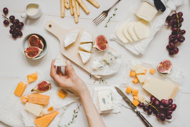 Różnorodni typ ser z owoc i przekąskami na drewnianym bielu stole Odgórny widok obrazy stock