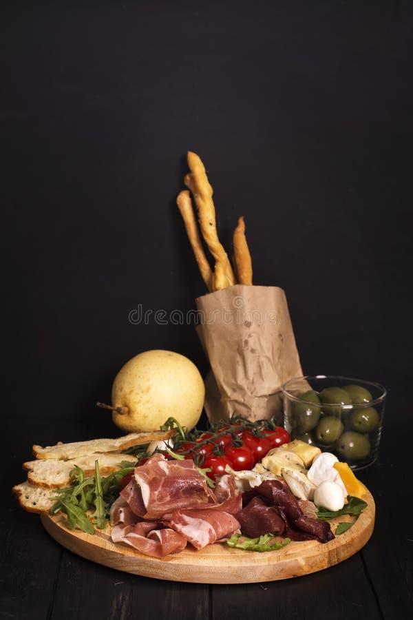 Różnorodni typ włoskie zakąski: baleron, ser, grissini, oliwki, owoc obraz royalty free