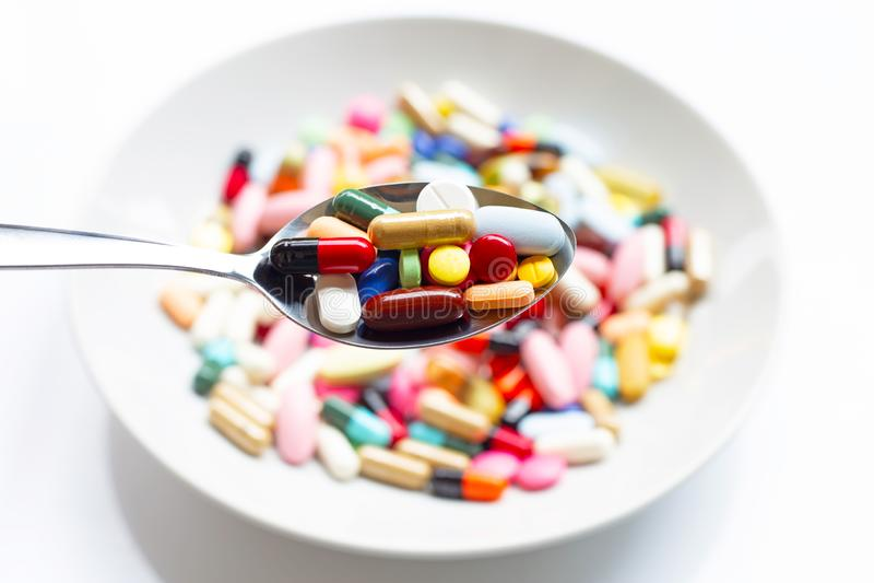 Różnorodni typy pastylki, kapsuły i pigułki na łyżce z kolorowym medycyny tłem, fotografia stock