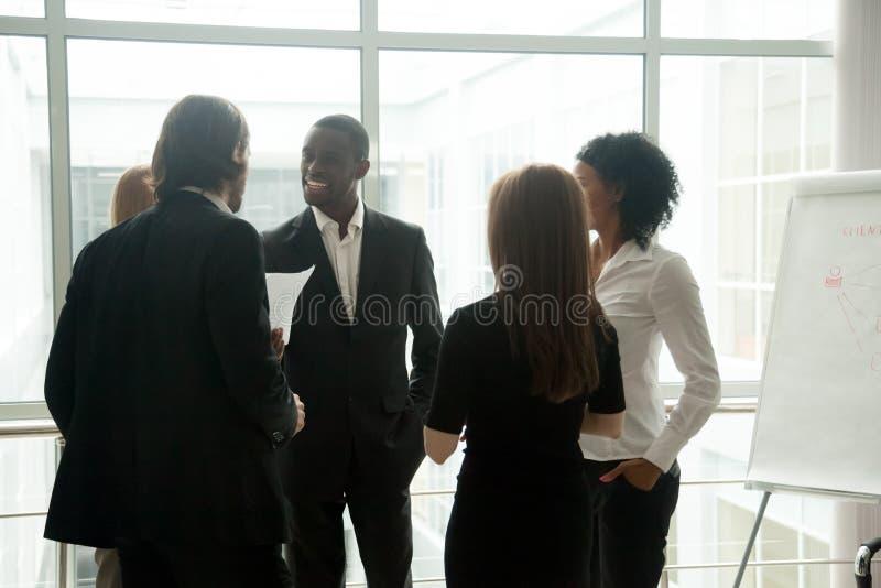 Różnorodni uśmiechnięci ludzie biznesu ma rozmowy trwanie tog obraz stock