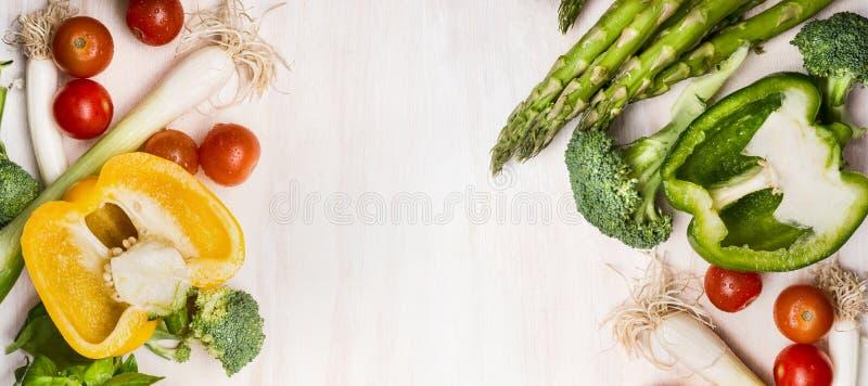 Różnorodni warzywa dla smakowitego kucharstwa z asparagusem, papryką, pomidorami, brokułami i cebulami na białym drewnianym tle,  zdjęcia royalty free