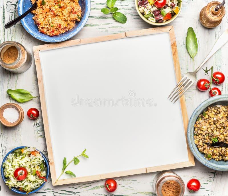 Różnorodni zdrowi jarscy sałatka puchary wokoło pustego białego chalkboard, odgórny widok zdjęcia royalty free