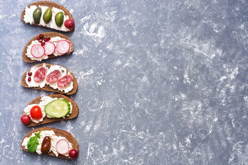 Różnorodność bruschetta z serem, kiełbasą i warzywami na szarym tle, Odgórny widok, przestrzeń dla teksta obraz royalty free