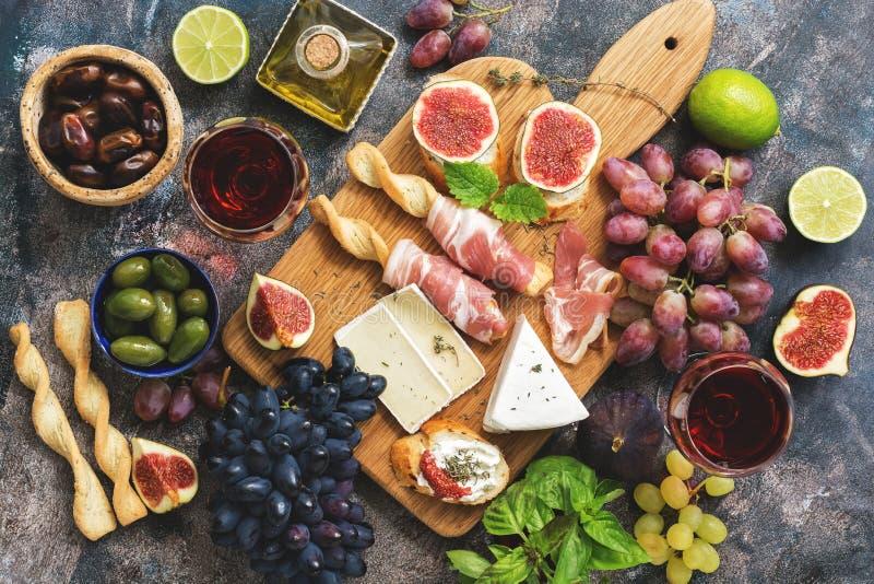Różnorodność przekąski, prosciutto, winogrona, wino, ser z foremką, figi, basil, oliwki na nieociosanym tle Odgórny widok, mieszk obraz stock