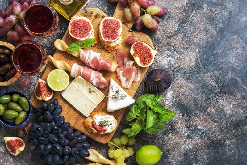 Różnorodność zakąska, prosciutto, winogrona, wino, ser z foremką, figi, oliwki na nieociosanym tle Śródziemnomorska przekąska wie zdjęcie royalty free
