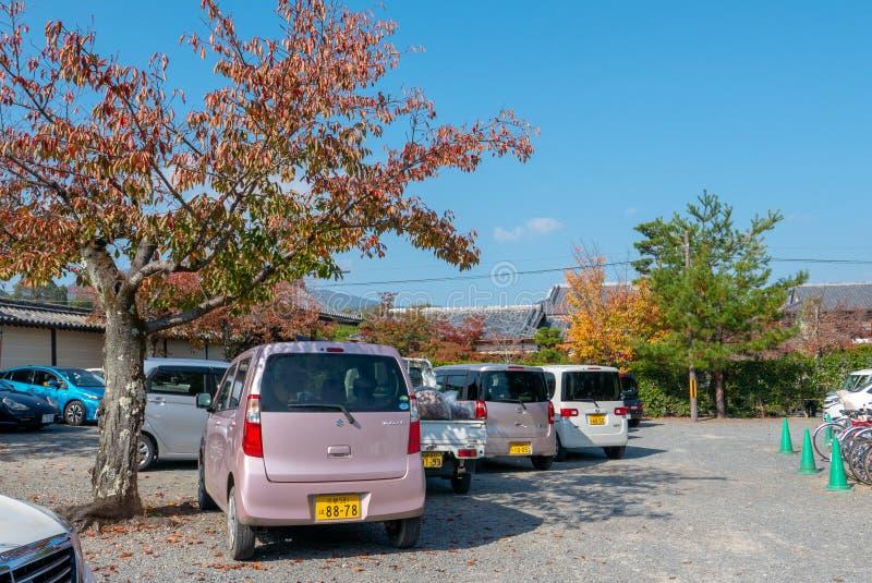 Różnorodny Kei samochodów park pod drzewami podczas jesieni w Arashiyama, Japonia zdjęcia royalty free