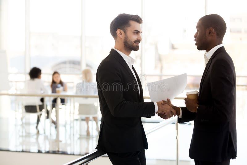 Różnorodny kolegi uścisk dłoni w korytarzu ma przypadkową rozmowę zdjęcia stock
