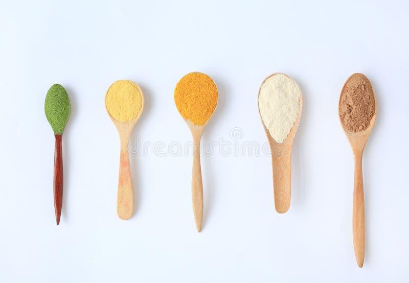 Różnorodny kolorowy proszek w różnych drewnianych łyżkach odizolowywać na białym tle obraz royalty free