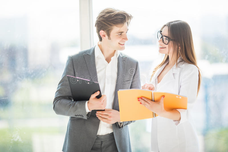 Różnorodny mężczyzna i kobiety biznes zespala się przy ich firma budynku biurowego odprowadzeniem w sala i disscuss nad notatnika zdjęcie stock