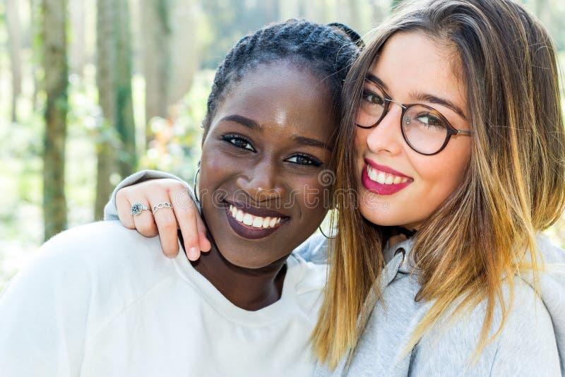 Różnorodny portret dwa atrakcyjnej nastoletniej dziewczyny outdoors zdjęcie royalty free