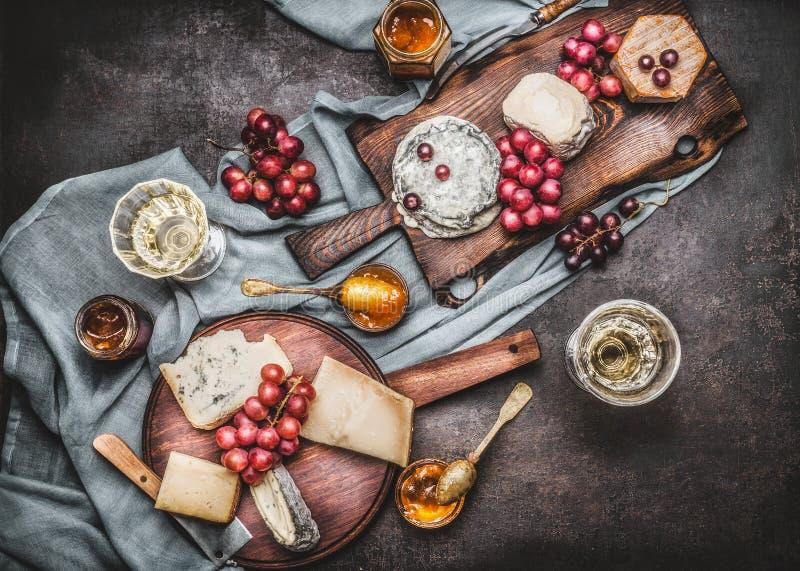 Różnorodny ser słuzyć na nieociosanych tnących deskach z winogronem i winem, ciemny rocznika tło obrazy stock