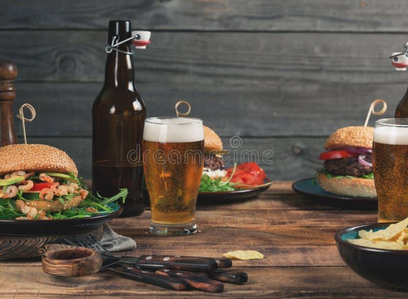 Różny hamburgerów, przekąski i lager piwo na drewnianym stole, zdjęcia stock