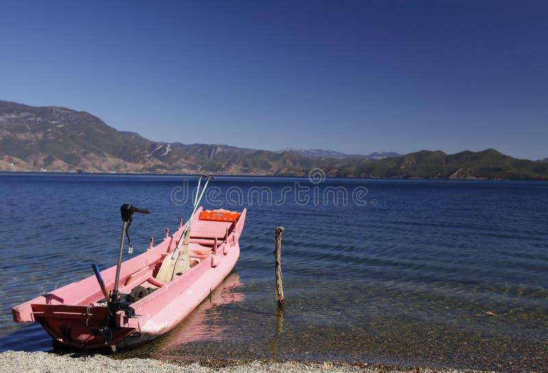 Różowa łódź rybacka na Lugu jeziorze otaczającym śnieżną górą obraz royalty free