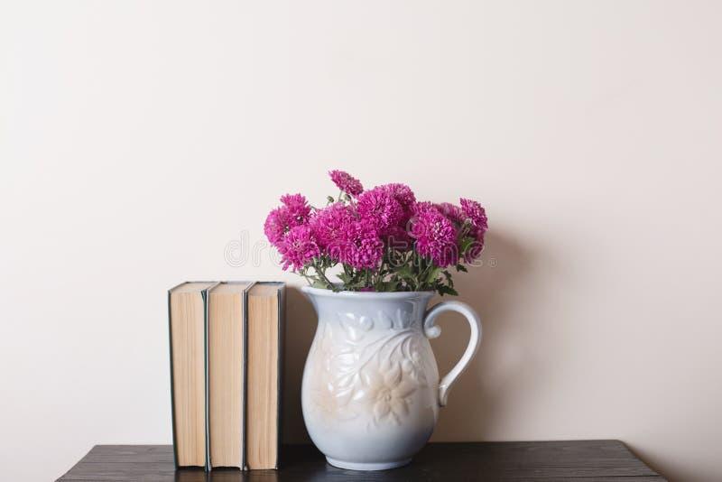 Różowa chryzantema w glinianej rarytas wazie, książkach na drewnianym stole i fotografia stock