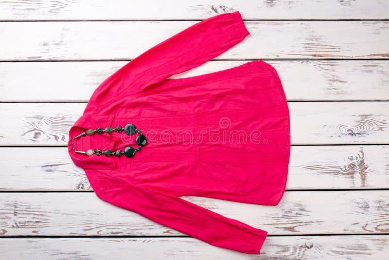 Różowa czerwona kobiety ` s koszula z kolii biżuterią fotografia stock