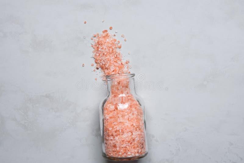 Różowa Himalajska sól w rocznik Szklanej butelce Rozlewającej na Popielatym Kamiennym Tabletop Wellness zdroju Zdrowej diety odży obrazy royalty free