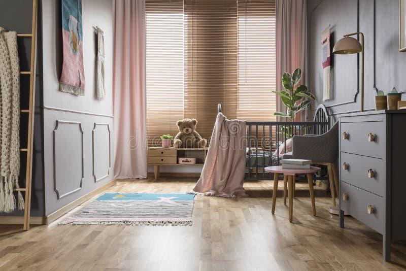 Różowa koc na dzieciaka ` s łóżku w jaskrawym popielatym izbowym wnętrzu z plus obraz stock