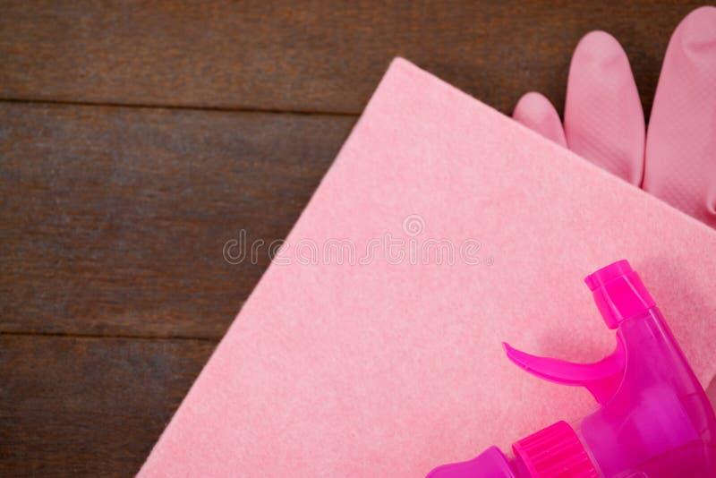 Różowa kolor kiści butelka, gąbka i rękawiczka na drewnianej podłoga, zdjęcia royalty free