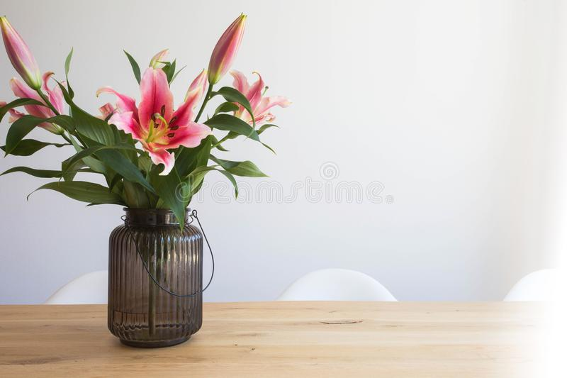 Różowa leluja kwitnie w wazie na drewnianym stole w wnętrzu przeciw białej ścianie w nowożytnym pokoju obraz royalty free