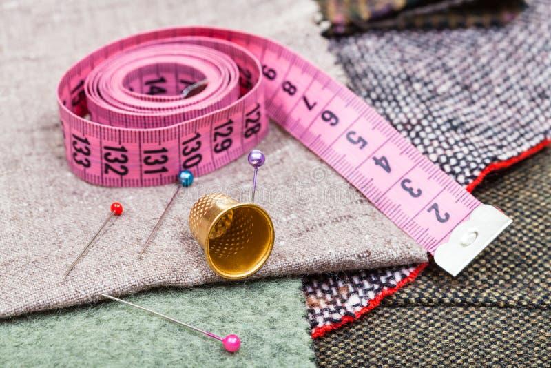 Różowa miara taśmy, szpilki, naparstek na tkaninie zdjęcie stock