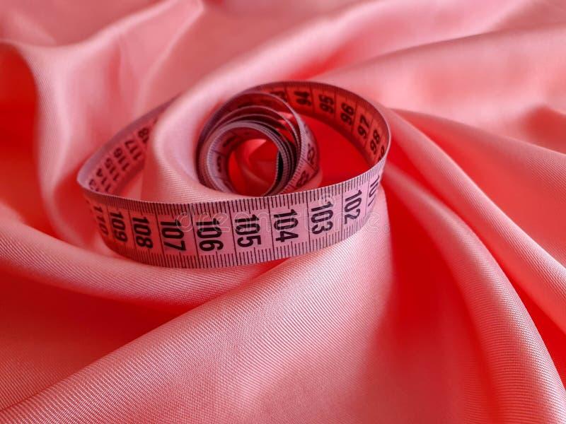 Różowa miara taśmy z czerni liczbami na białym naturalnego lub tkaniny tle Zamyka w górę widoku pomiarowa taśma Tematy: dieta, fotografia royalty free