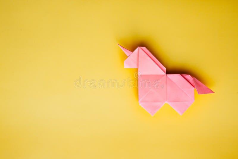 Różowa origami jednorożec na żółtym tle fotografia royalty free