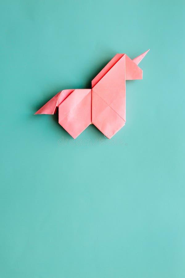 Różowa origami jednorożec na cyan błękitnym tle obraz stock