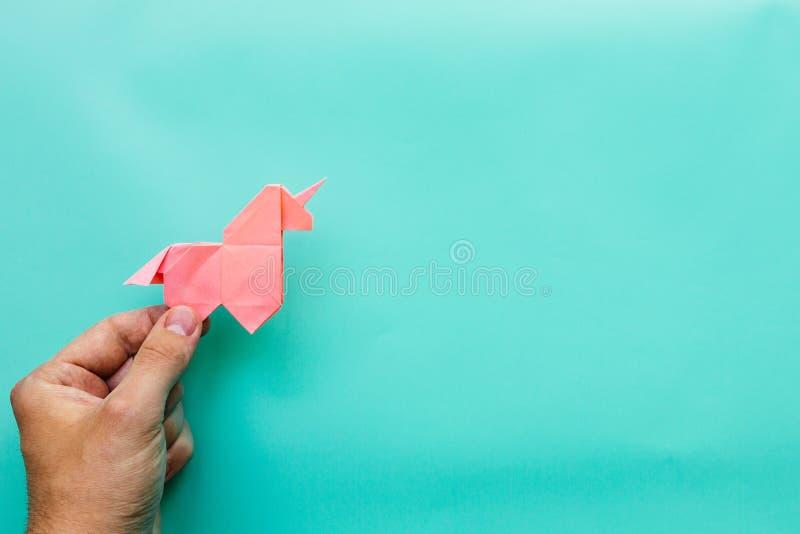 Różowa origami jednorożec na cyan błękitnym tle fotografia royalty free