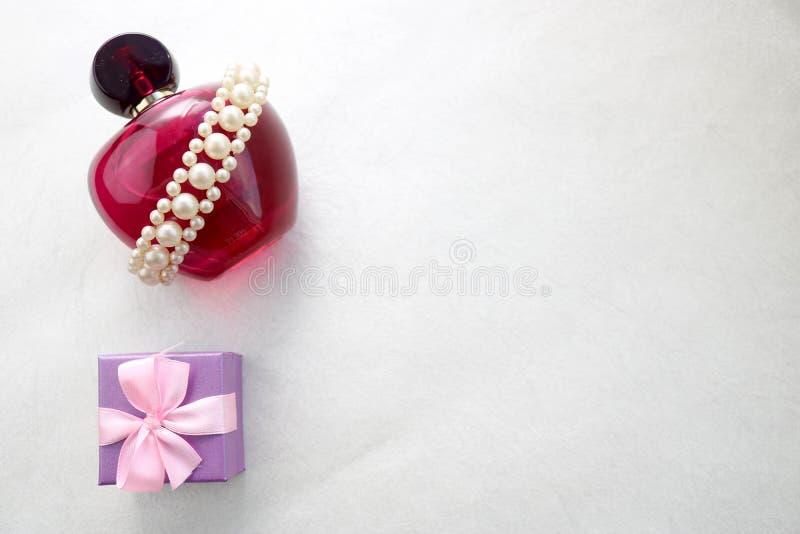 Różowa piękna szklana przejrzysta butelka żeński pachnidło dekorował z białymi cennymi perłami f, błękitny mały miejsce i prezent obrazy stock