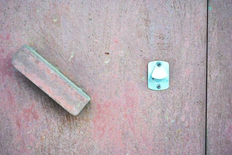 Różowa podława farba na żelaznym drzwi i rękojeść z nowym nierdzewnym keyhole zdjęcie royalty free