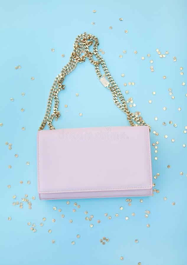 Różowa torba na złocistym łańcuchu Złoci cekiny niebieska tła zdjęcie royalty free
