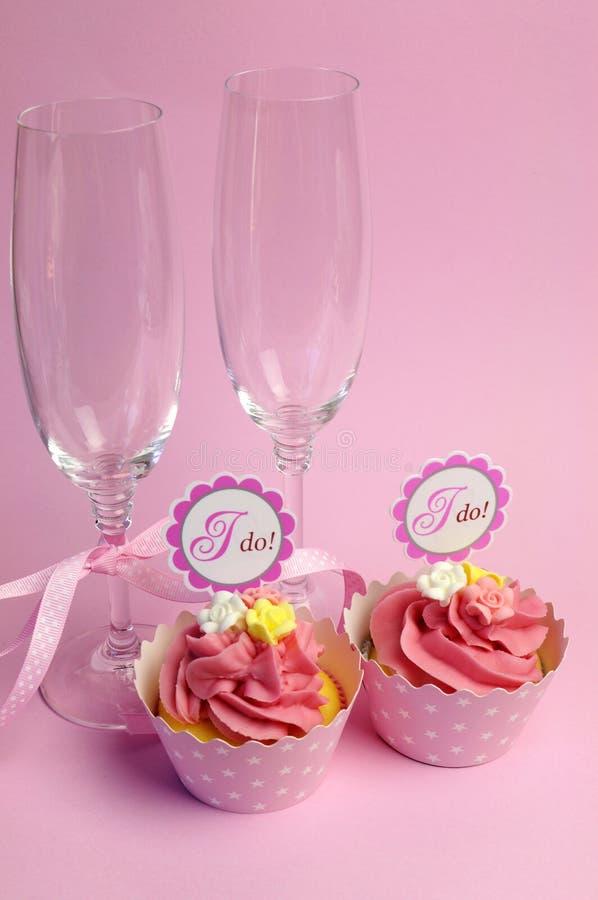 Różowe ślubne babeczki z Robię numer jeden i szampańskim szkłom zdjęcia royalty free