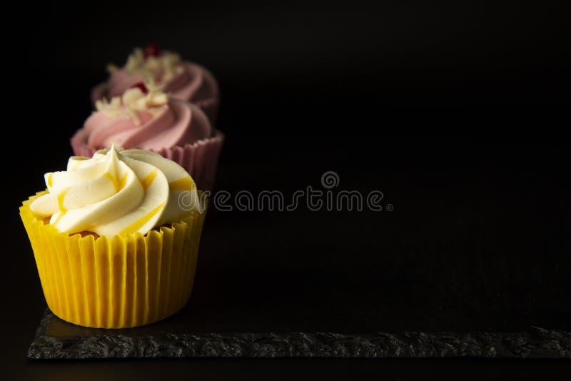 Różowe i żółte babeczki przeciw czarnego tła, urodziny lub przyjęcia babeczkom, Partyjny słodki jedzenie, desery kosmos kopii fotografia royalty free