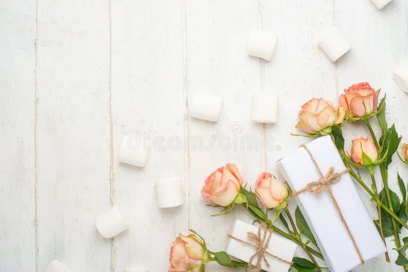 Różowe róże na białym drewnianym tle z cukierkami, świąteczny tło, rocznica, ślub, walentynka dzień Mieszkanie nieatutowy odgórny zdjęcie royalty free