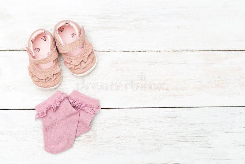 Różowe skarpety i buty dla małej dziewczynki na białym drewnianym backgroun zdjęcie royalty free